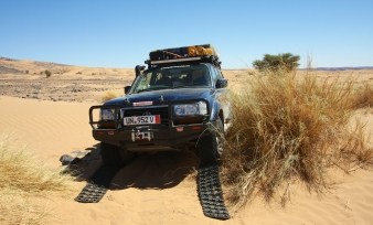In the middle of the Sahara stuck in sand between two bushes. Sand tracks, four-wheel low, and lockers do the trick.