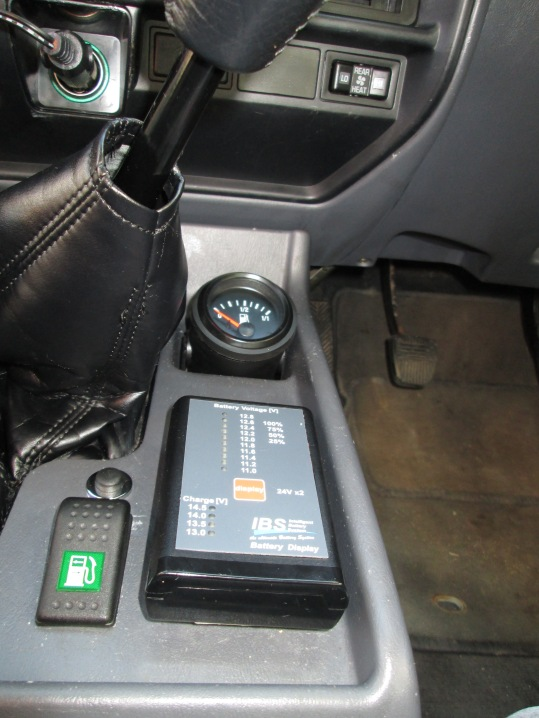 Fuel gauge for auxiliary fuel tank, switch that controls the valve that places either the main or auxiliary fuel tank in operation, and IBS battery monitor display for the third battery (accessories).